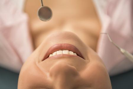 odontologo: Una mujer está sonriendo mientras está en el dentista.