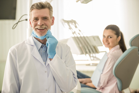 Portrait of a smiling senior dentist on the background his patient in dental clinic.