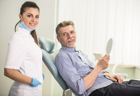 Female dentist with his senior client in dental clinic and looking at camera.
