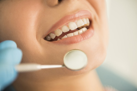 Close up of Dentist hands working attractive female teeth.