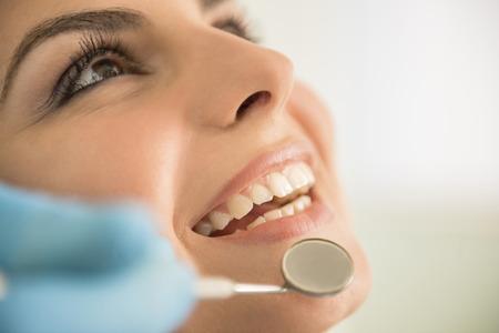 femmes souriantes: Gros plan des mains de dentiste de travail attrayantes dents femmes. Banque d'images