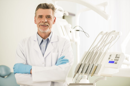 Portrait of a smiling senior dentist in dental clinic.