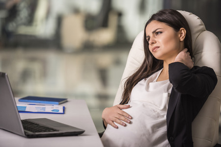 Tired pregnant woman. Pregnant businesswoman holding neck in office.
