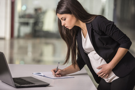 leave: Pregnant adult businesswoman working  at her working place in office.