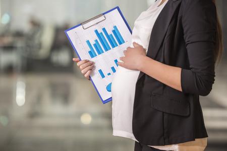 Detailopname. Zwangere volwassen zakenvrouw werken op haar werkplek in het kantoor. Stockfoto