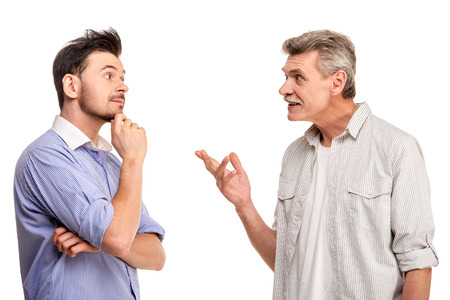 Senior father with adult son talking, isolated white . Foto de archivo
