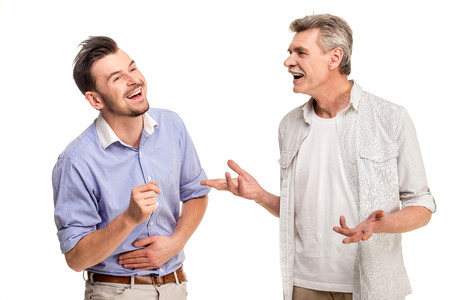 generation gap: Senior father with adult son talking, isolated white . Stock Photo