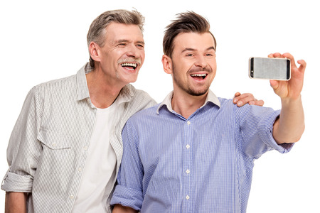 mature old generation: Adult son with senior father doing selfie, isolated white . Stock Photo