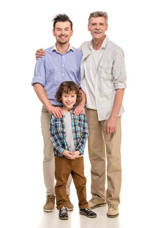 Full length. Grandfather, father and son looking at camera isolated a white background. Stock Photo