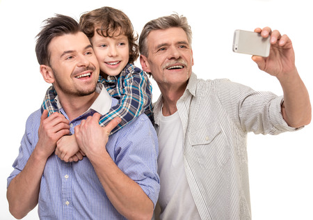 Generation portrait. Grandfather, father and son doing selfie, isolated a white background.