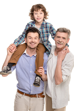 Generation portrait. Grandfather, father and son looking at camera isolated a white background. photo