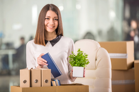 proffesional: Smiling young businesswoman packing boxes and looking on camera in office.