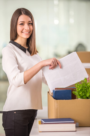 proffesional: Smiling young businesswoman packing boxes in office. Stock Photo
