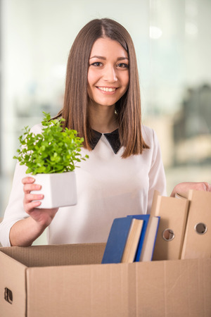 Smiling young businesswoman packing boxes in office. photo