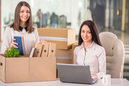 Smiling young businesswomen working and packing boxes in office. photo