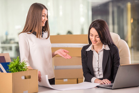 new office space: Smiling young businesswomen planning out their new office space. Stock Photo
