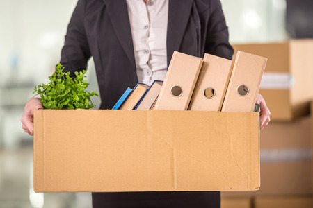 going: Close-up. Smiling young businesswoman holding cardboard box with her things. Stock Photo