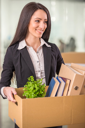 belongings: Smiling young businesswoman holding cardboard box with her things. Stock Photo