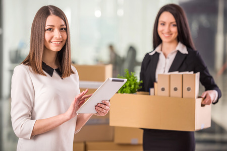 Two female businesswomen moving into a new office. photo