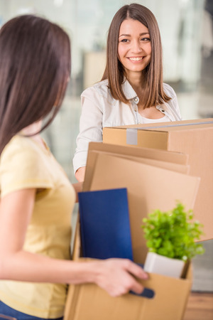 Two businesswomen surrounded by boxes in their new office. photo