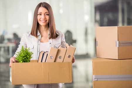 Young woman holding box with things in office. photo