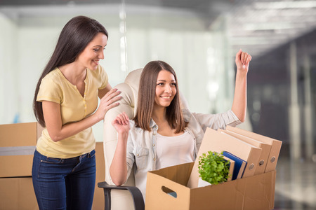Two adult businesswomen moving into a new office. photo