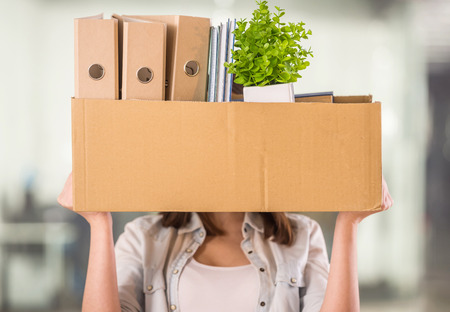 unemployed dismissed: A woman holding up a box in an office setting with other boxes