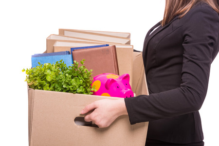 Side view. Business woman holding box with office items.