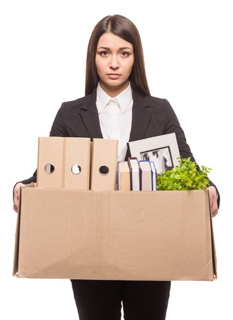 Business woman holding box with office items. isolated on white .