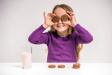 milk chocolate: Cute little girl holding cookie while sitting at the table on grey . Stock Photo