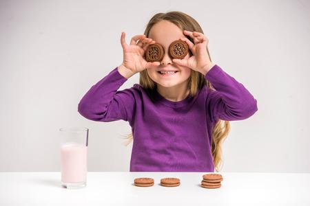 Niña linda que sostiene la galleta mientras está sentado en la mesa en gris.