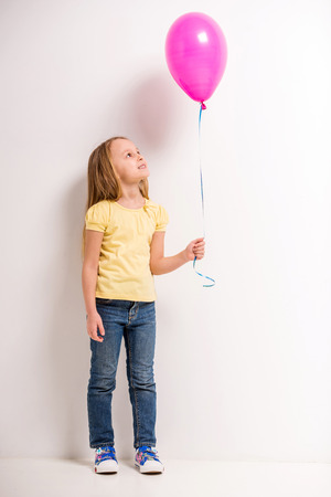 ni�as peque�as: Longitud total. Ni�a linda que sostiene el globo de color rosa sobre fondo gris.