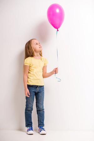 mignonne petite fille: Toute la longueur. Mignon petite fille tenant ballon rose sur fond gris.