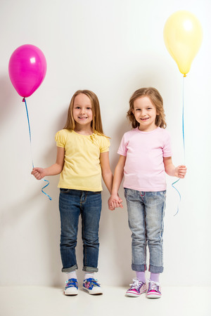 pink balloons: Best friends. Two cute little girls holding balloons on grey background.