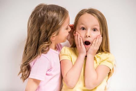 Girl telling a secret her friend on grey background.