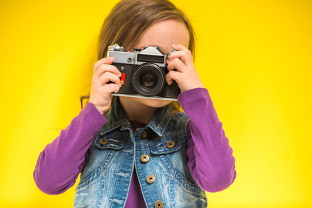 photographers: A little cute girl making photo on yellow background. Stock Photo