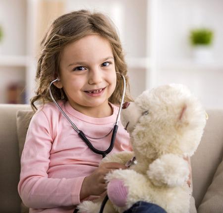 enfant malade: La petite fille mignonne avec ours en peluche et d'un st�thoscope. Banque d'images