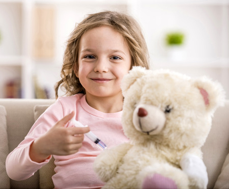 Little girl makes injection to teddy bear. Smiling and looking at the camera. Archivio Fotografico