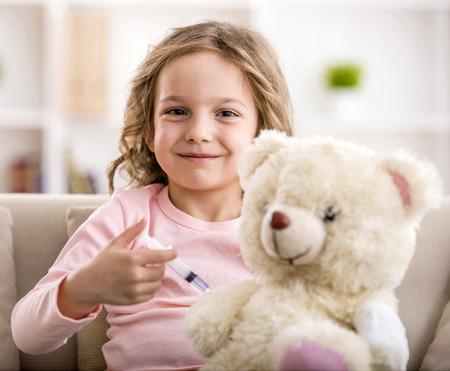 La niña hace inyección para el oso de peluche. Sonriendo y mirando a la cámara.