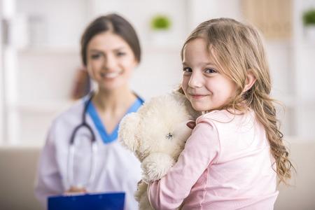Молодой улыбается женщина-врач и ее маленький пациент с плюшевым медведем. Фото со стока
