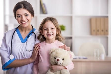 Jonge lachende vrouwelijke arts en haar weinig patiënt met teddybeer.