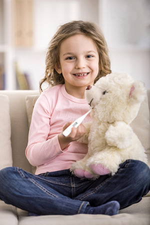 Cute little girl is measure the temperature teddy bear. photo
