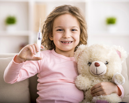 cute teddy bear: Little girl makes injection to teddy bear. Smiling and looking at the camera. Stock Photo