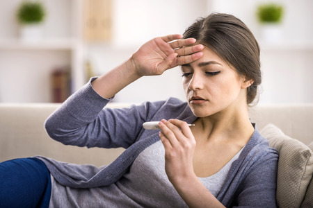 chory: Młoda kobieta patrzy na termometr. Ona ma gorączkę.