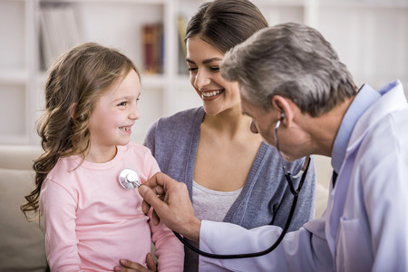 doctor stethoscope: Pediatrician checks breath stethoscope a little girl in the arms of mother.