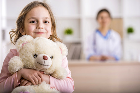hospital patient: Little girl with teddy bear is looking at the camera. Female doctor on background.