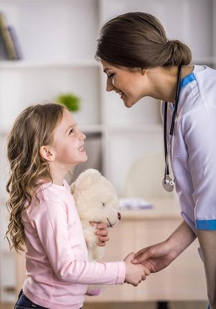 enfant malade: Vue de côté de la jeune femme médecin souriante et son petit patient avec ours en peluche.