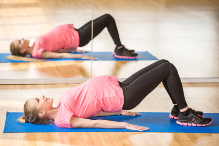 Beautiful pregnant woman at gym fitness exercise practicing aerobics on mat.