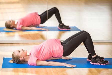embarazada feliz: Hermosa mujer embarazada en el ejercicio de fitness gym practicar aeróbicos en la estera.