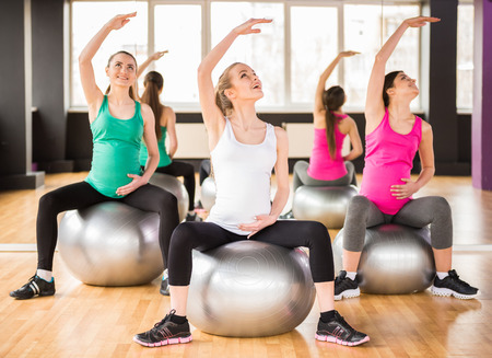 embarazada: Fitness, deporte y estilo de vida concepto - tres mujeres embarazadas con pelotas de ejercicio en el gimnasio.